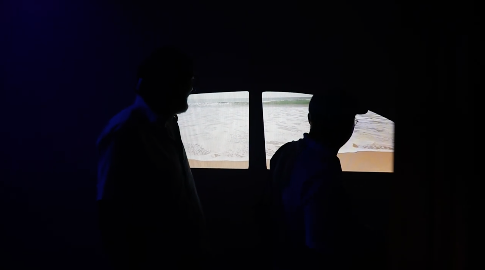 Two men in the dark experiencing an Interactive Digital Signage experience