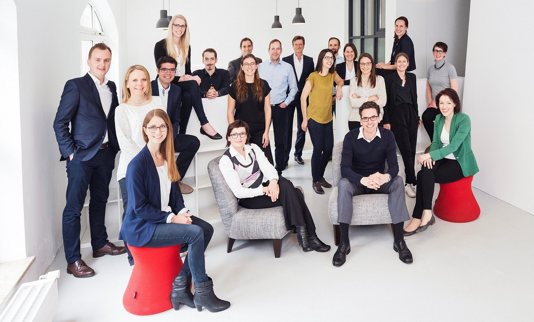 Group of young employees sitting and standing in a white room.