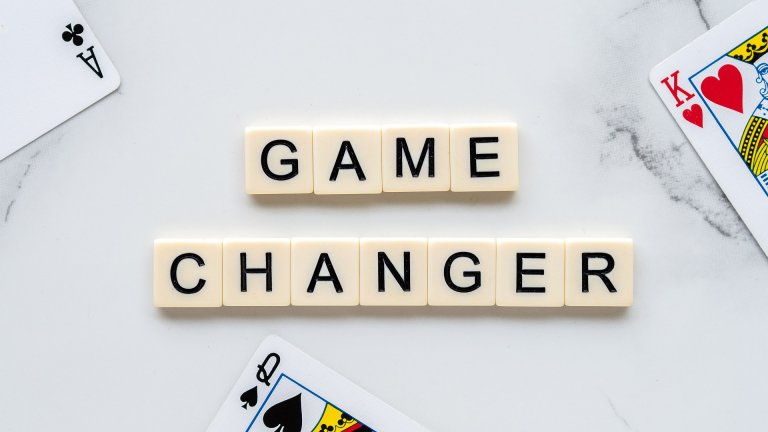"Scrabble tiles spelling ""Game Changer"" on table top."