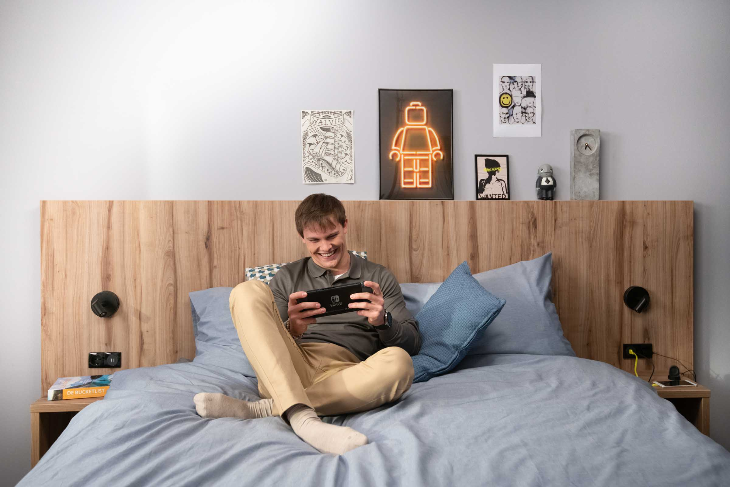 Guy on the bed at OurDomain Amsterdam Diemen playing with nintendo videogames