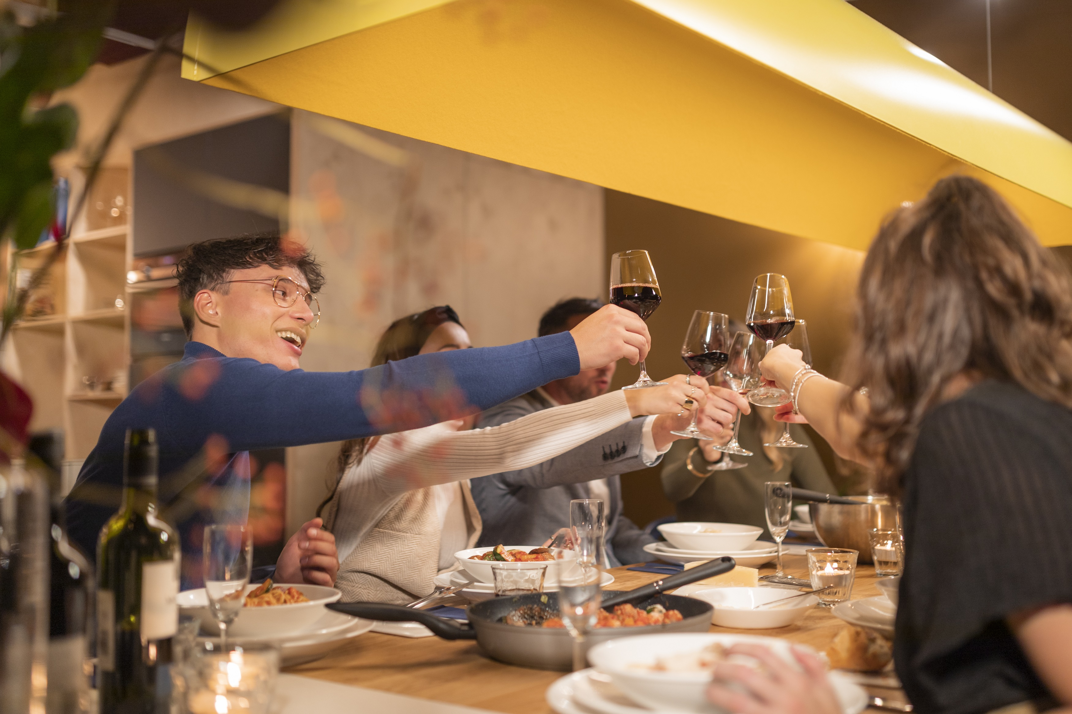 Residents cheering around the dinner table at OurDomain Amsterdam Diemen