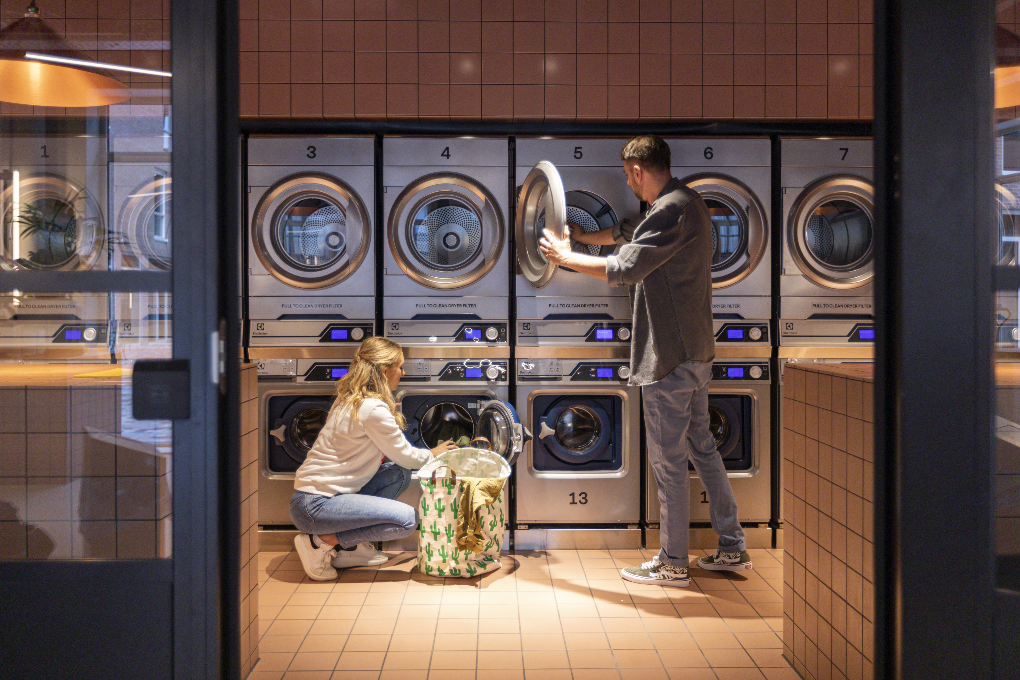 Residents doing their laundry at OurDomain Amsterdam Diemen