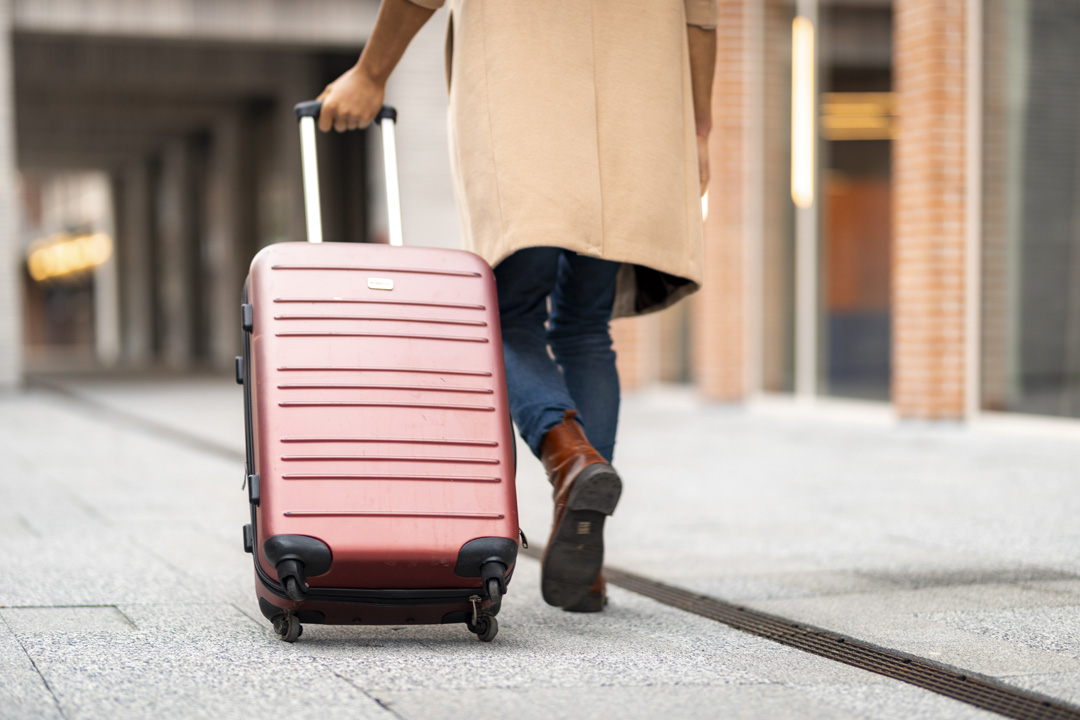 Man with beige coat dragging his red luggage