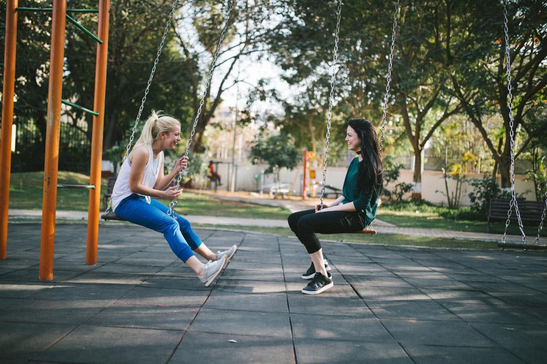girls talking outside on two swings