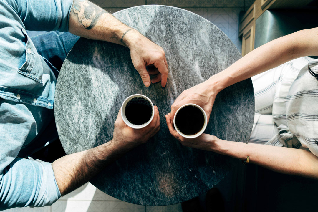 couple holding cups of coffee bird eye view of a coffee table