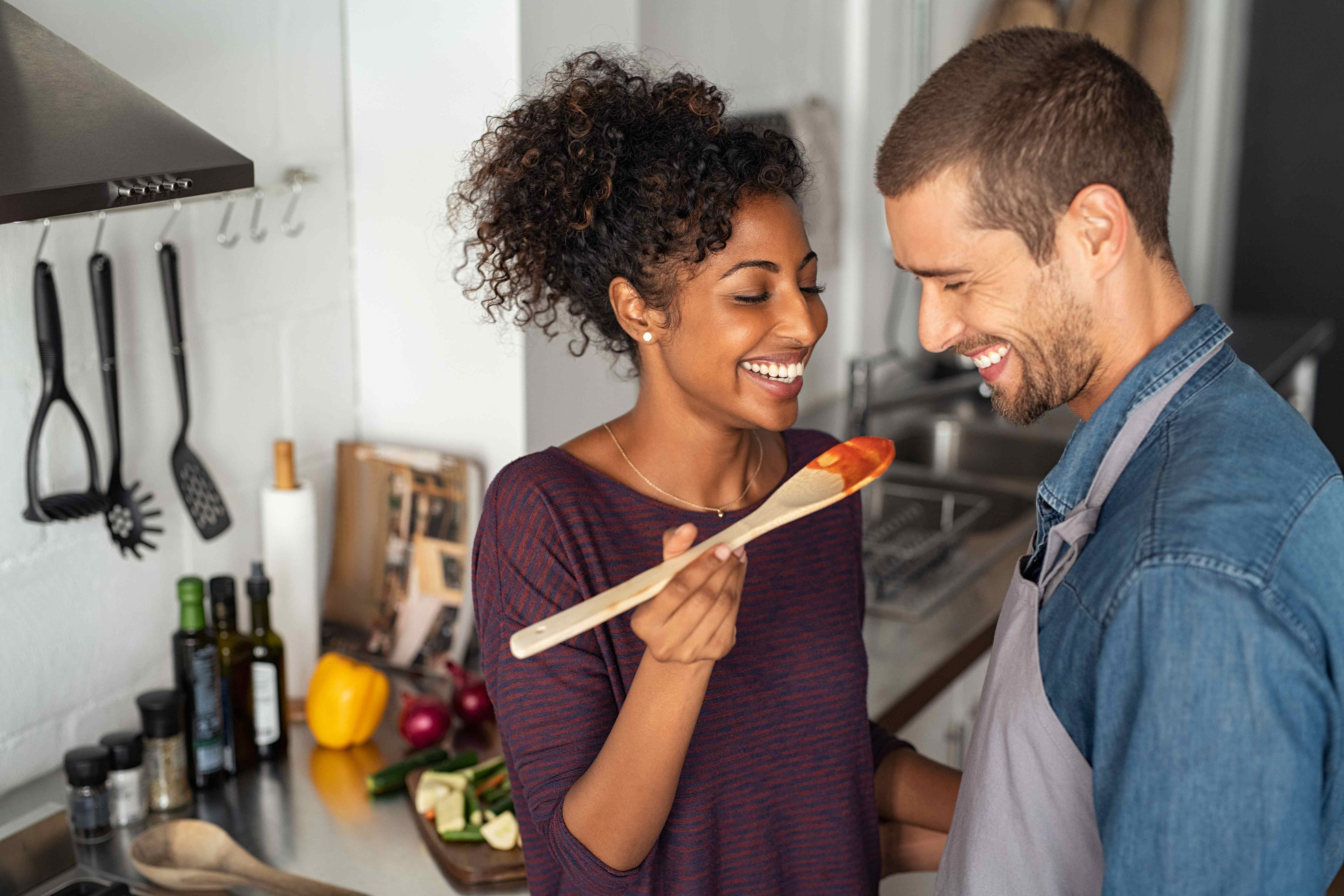 Couple laughing together while cooking in the kitchen