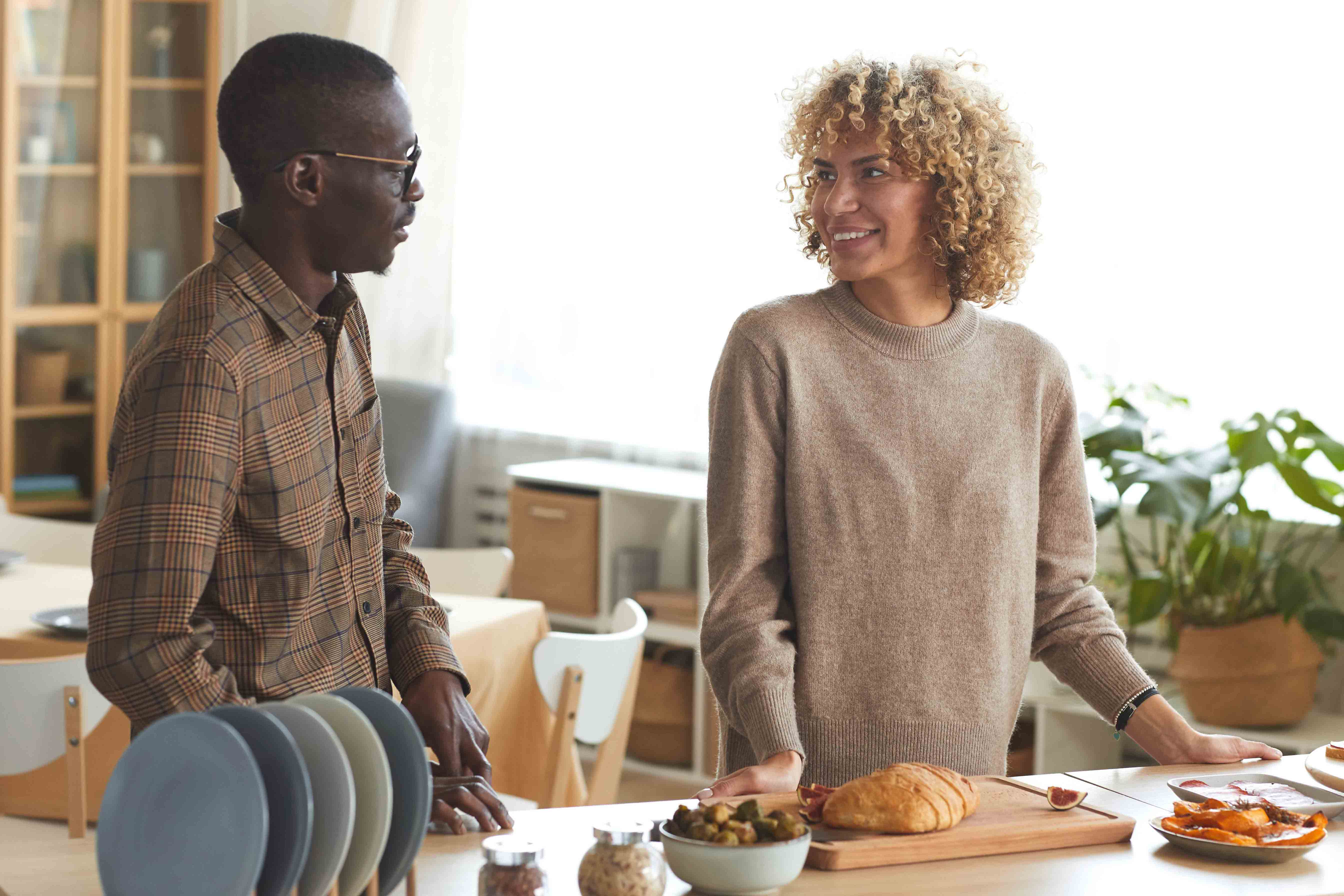 Interracial couple looking at each other in front of table with breakfast