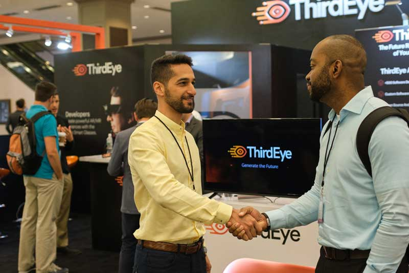 a sponsor and an end user shake hands after conversing about the technology