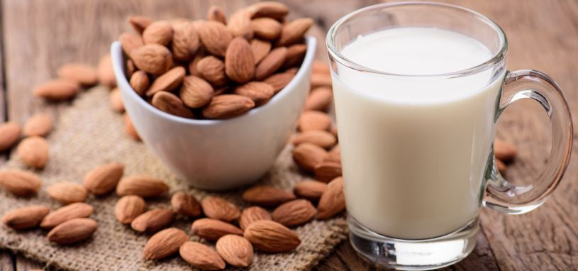 almond milk in a glass beside a bowl of almonds