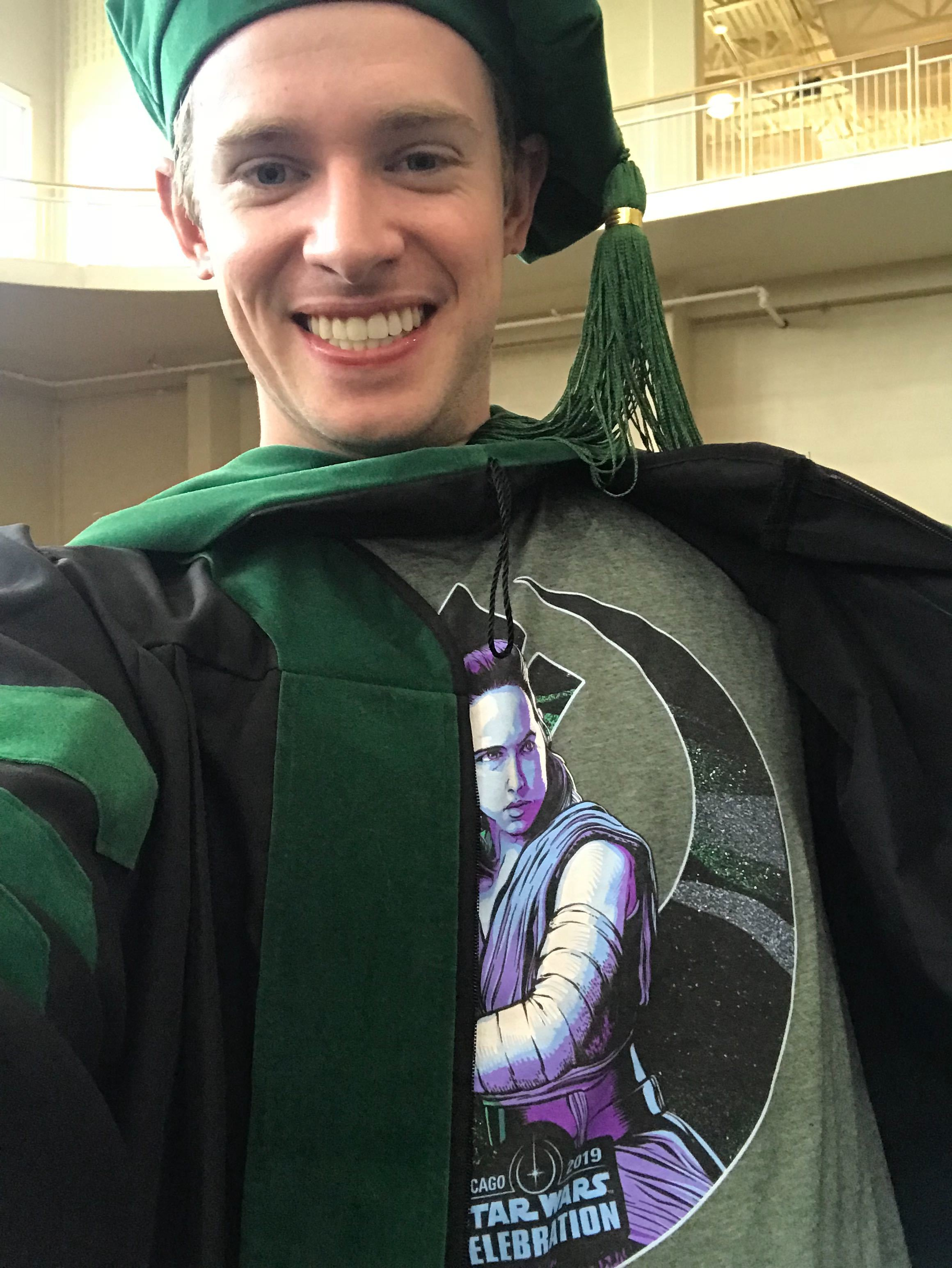 Corey with his Rey shirt graduating from medical school