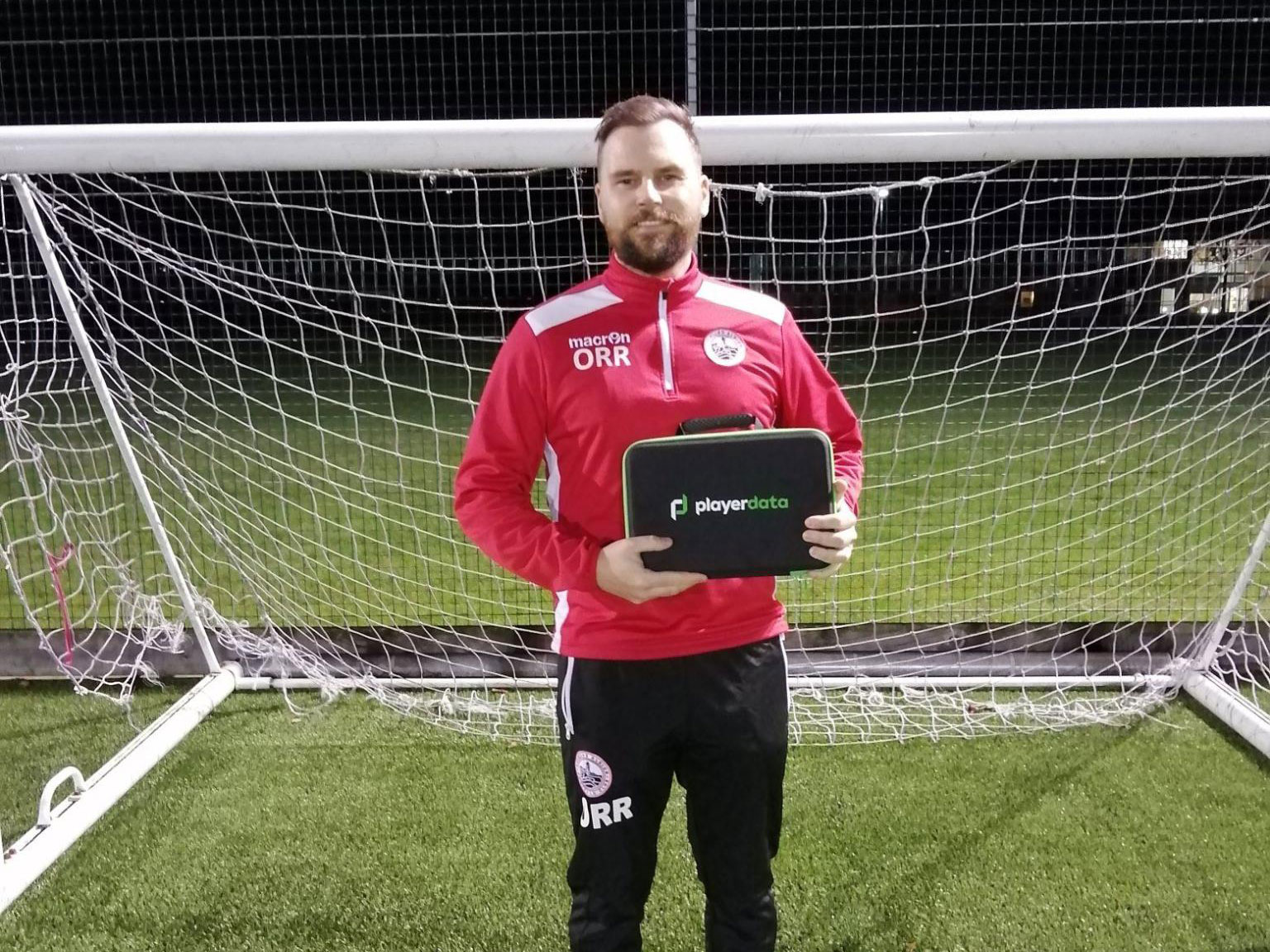 Man in front of goal holding PlayerData product
