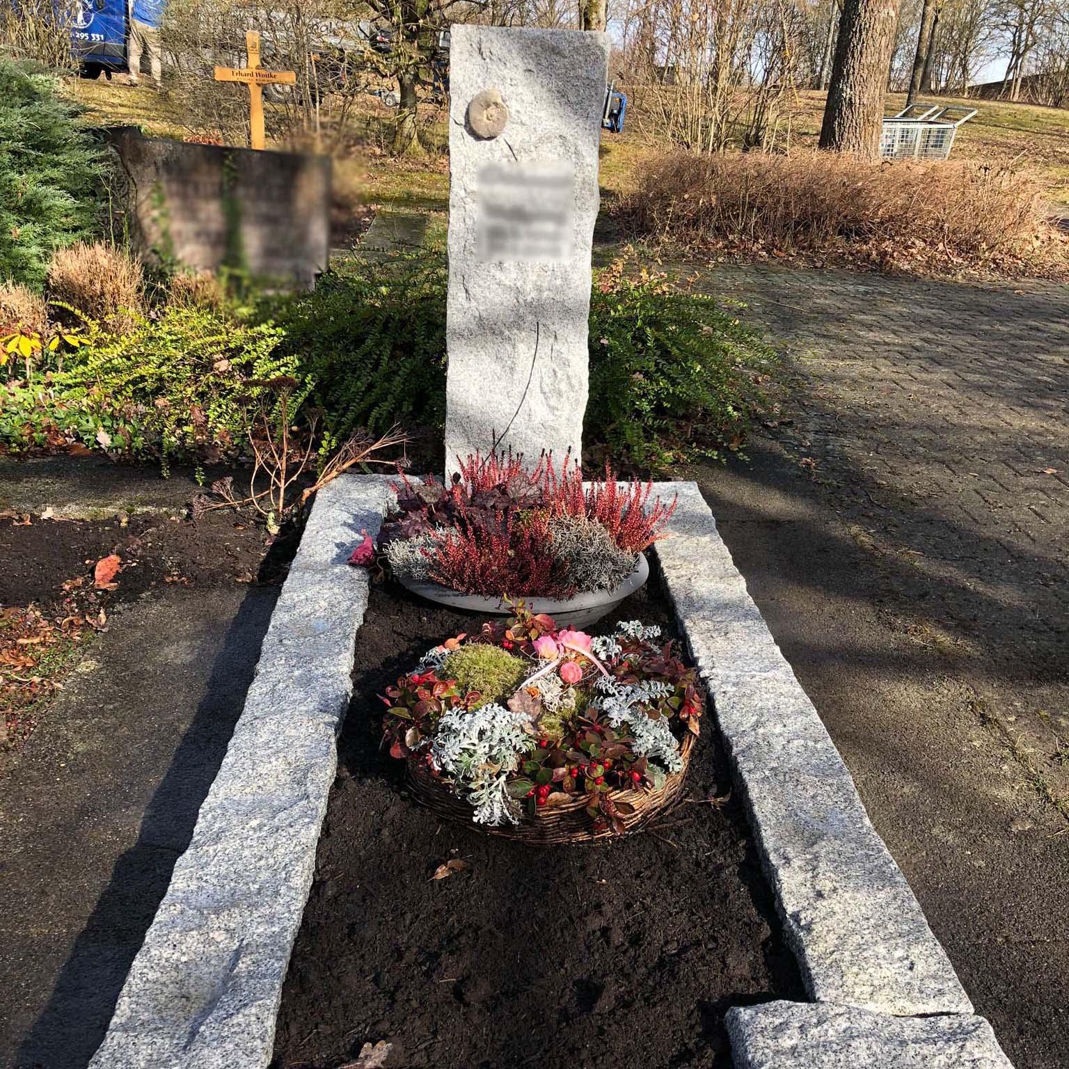 Einzelgrabstein mit Beschriftung und Kreuz
