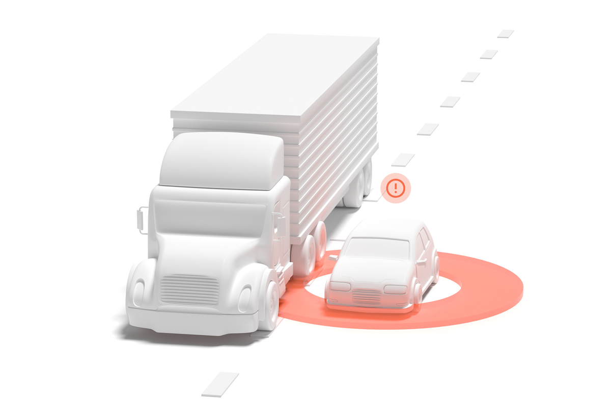 An autonomous vehicle drives carefully next to a large truck in virtual testing.