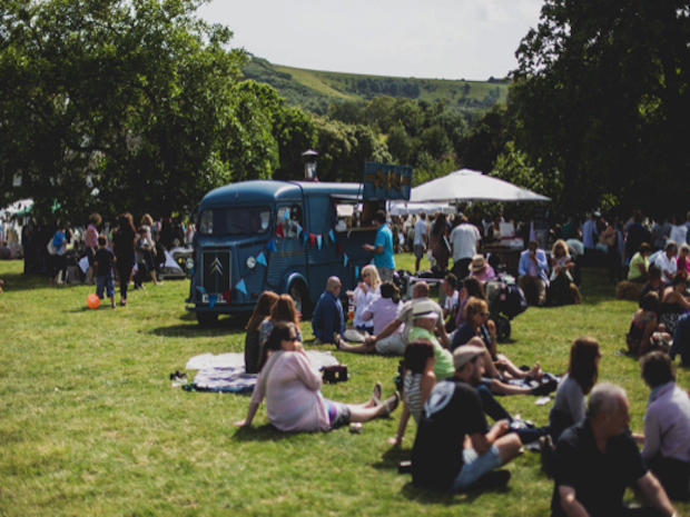 group of people sitting on grass at firle vintage fair with vintage vw van in the background