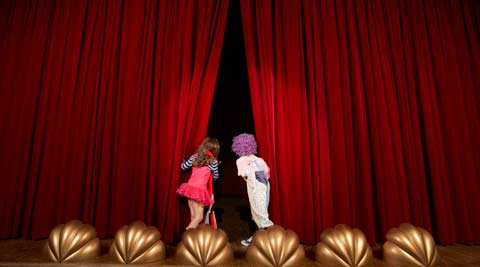 Two children peering behind a theatre curtain
