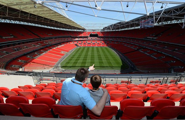 father and son looking out onto the Wembley Stadium pitch on a tour of the stadium