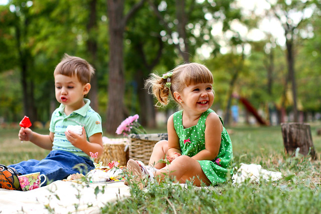 a girl and a boy in the park having a picnic