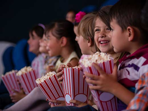 Children smiling at the cinema holding popcorn