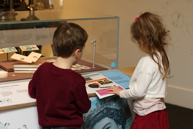 a little girl and boy at the bank of england museum looking at an exhibit