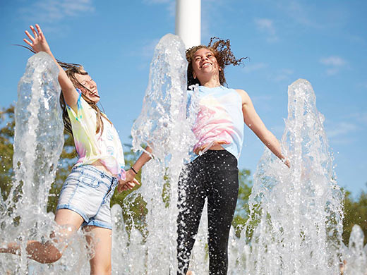 two girls splashing about in water jets on a hot day
