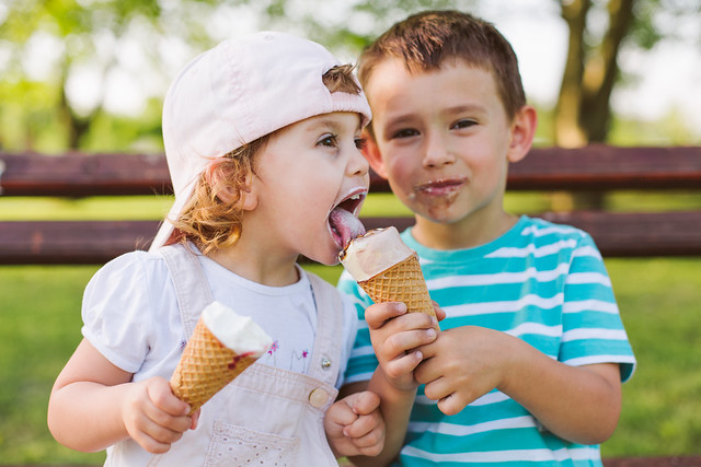 boy sharing ice cream with his little sister
