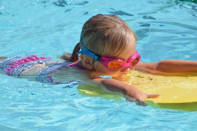 girl swimming with yellow float and pink goggles