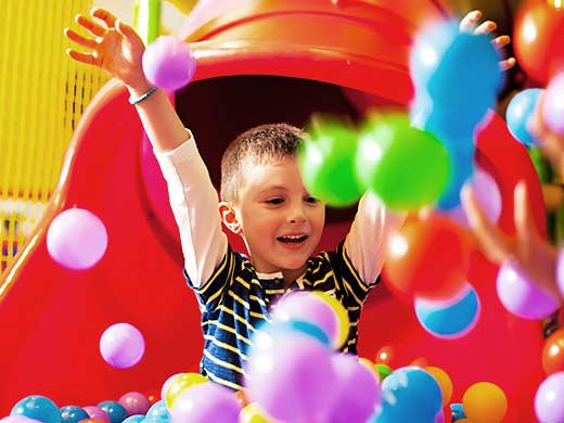 boy sliding down a slide into a ball pit at Hullabaloo Soft Play