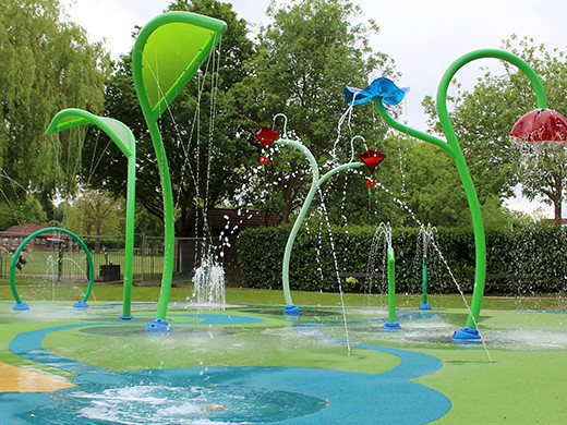splash pad in park with tropical sprinklers and colourful water jets