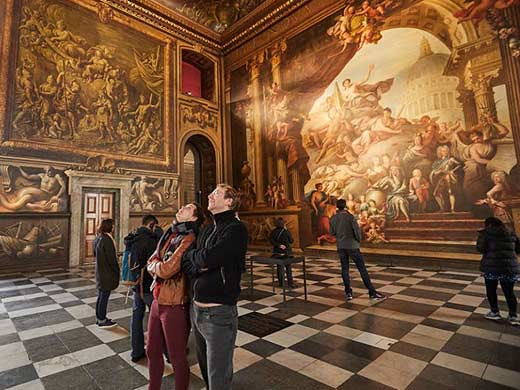 two adults marvelling at the greenwich attraction the painted hall