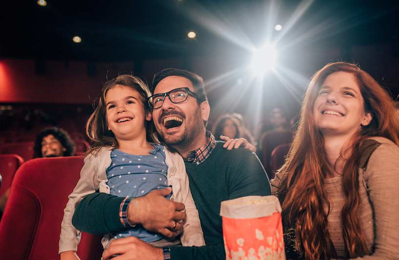 Parents with their daughter laughing at the theatre