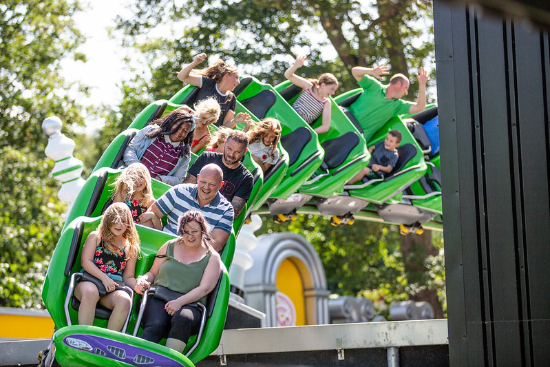 parents with their kids at a roller coster