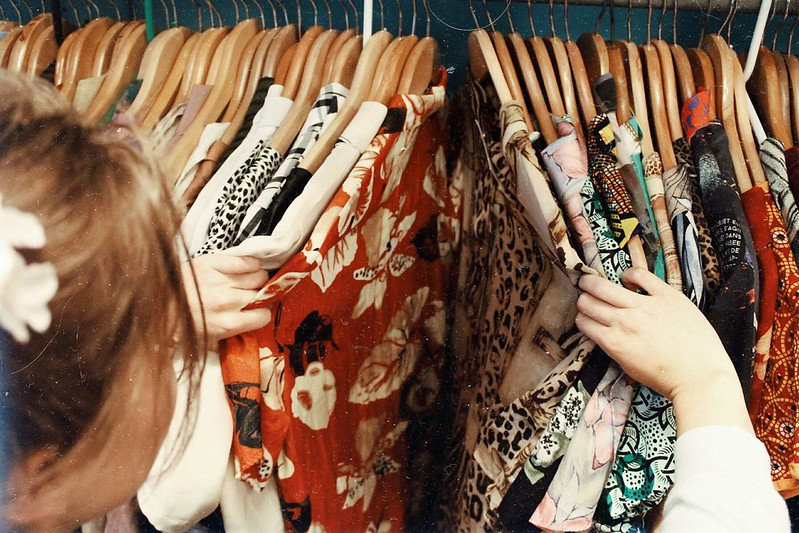 little girl looking through vintage clothes