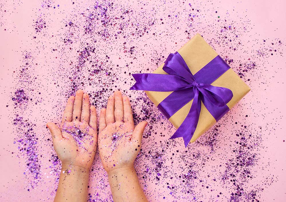 pink background with wrapped shoe box and hands covered in purple glitter