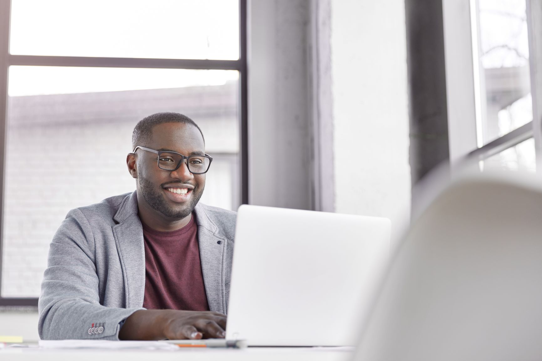Black male smiling at laptop during a video call