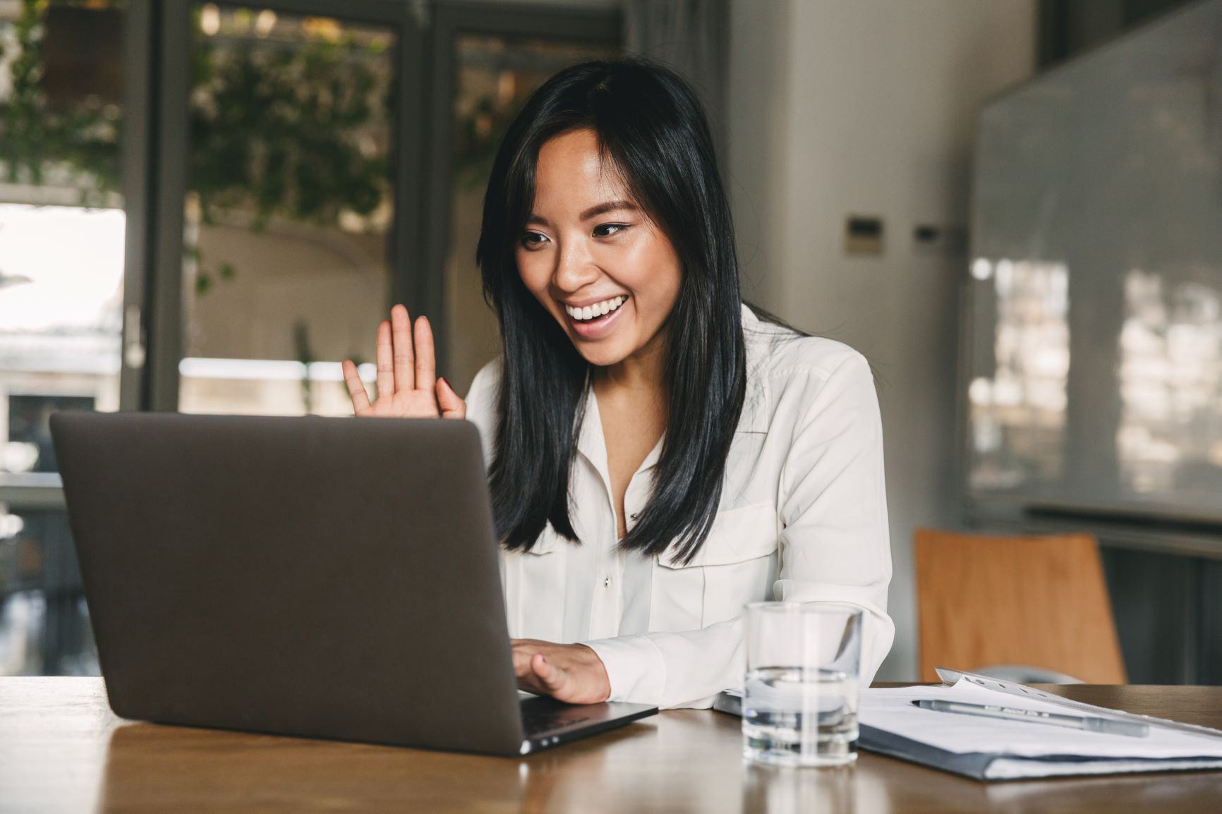 Asian female smiling and waving at laptop during video call
