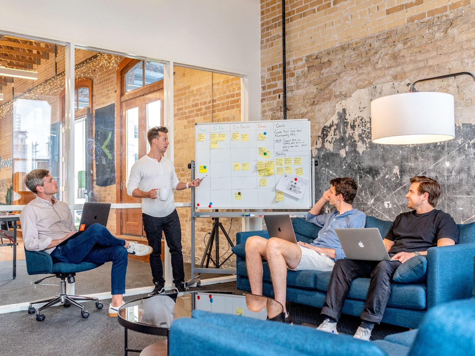 a meeting with four people discussing a whiteboard
