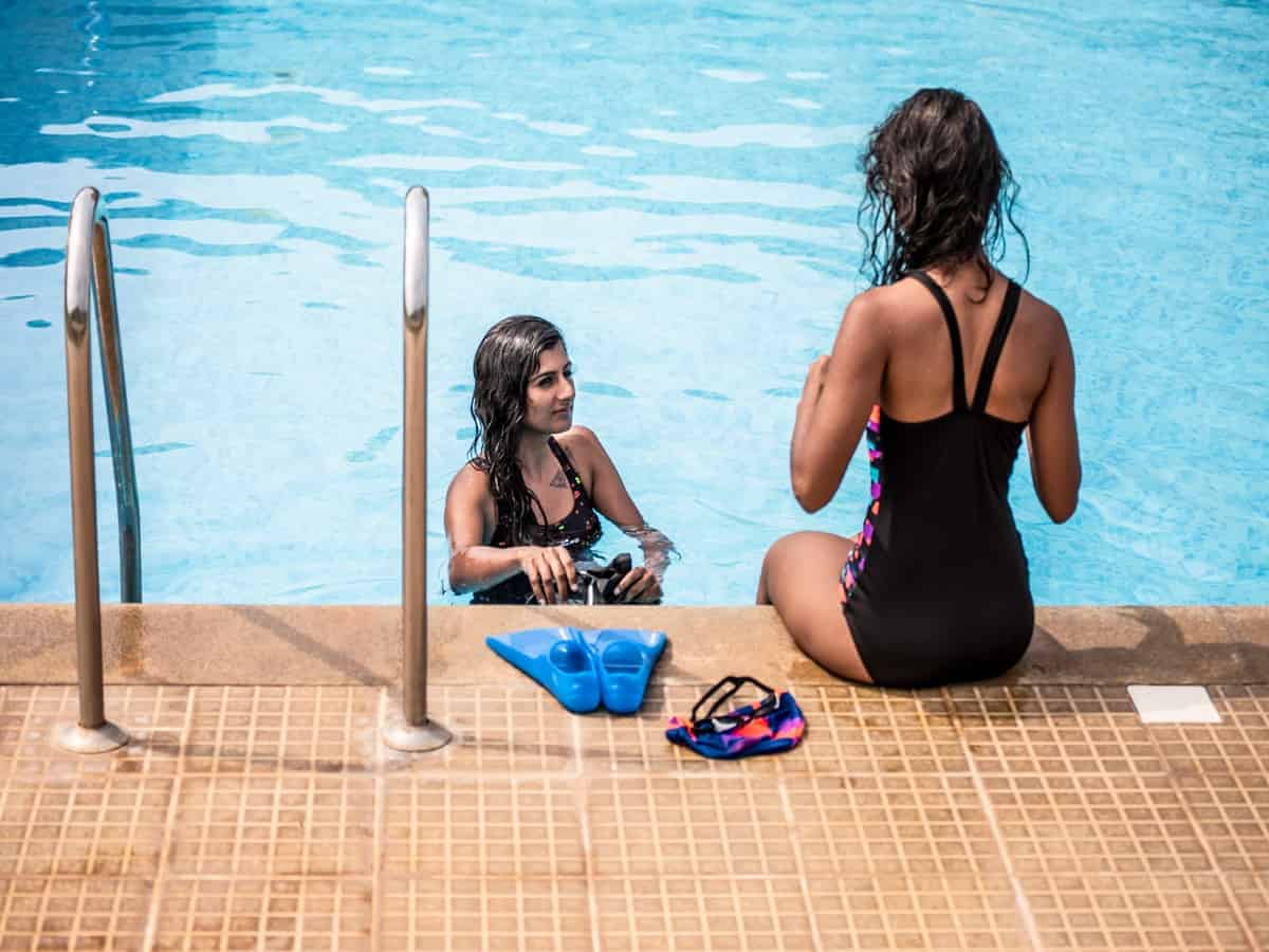 2 Girls sitting outside the pool