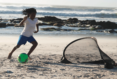 boy playing football on the beach