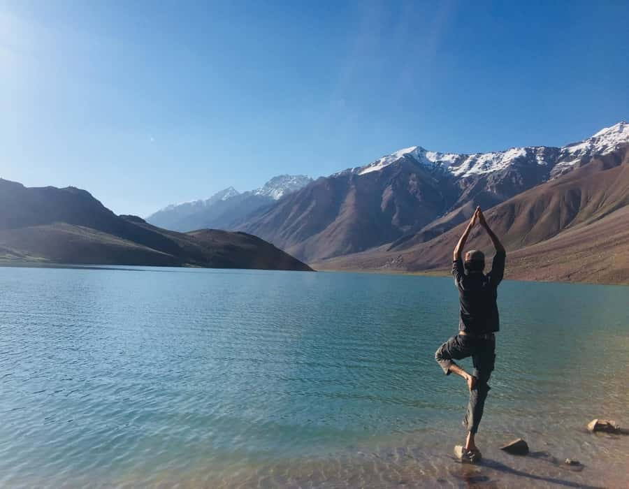 man standing in yoga posture in front of a lake