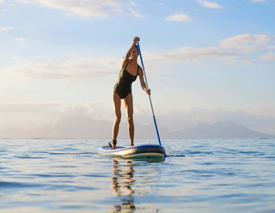 Women using stand up paddle while boarding