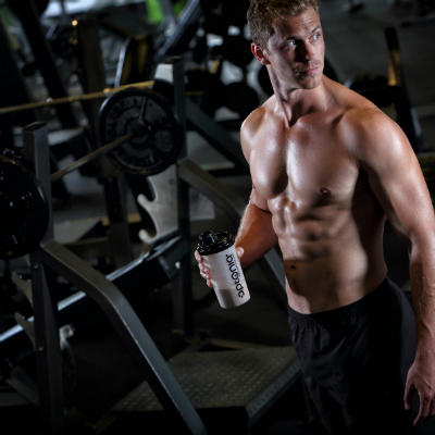 man drinking creatine in gym