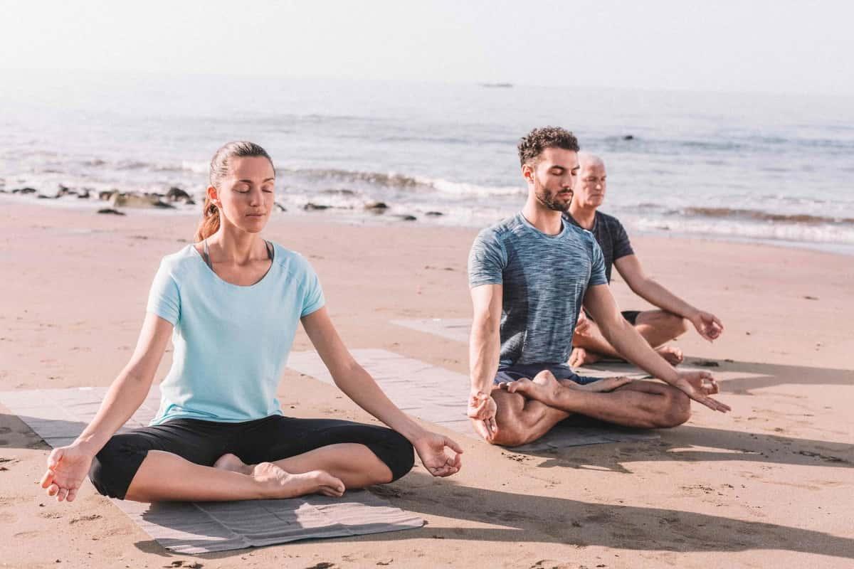 people sitting on seashore for meditation