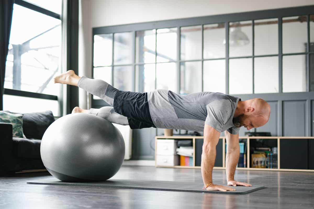 man doing pushups on gym ball