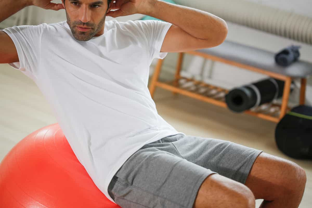 man stretching on gym ball