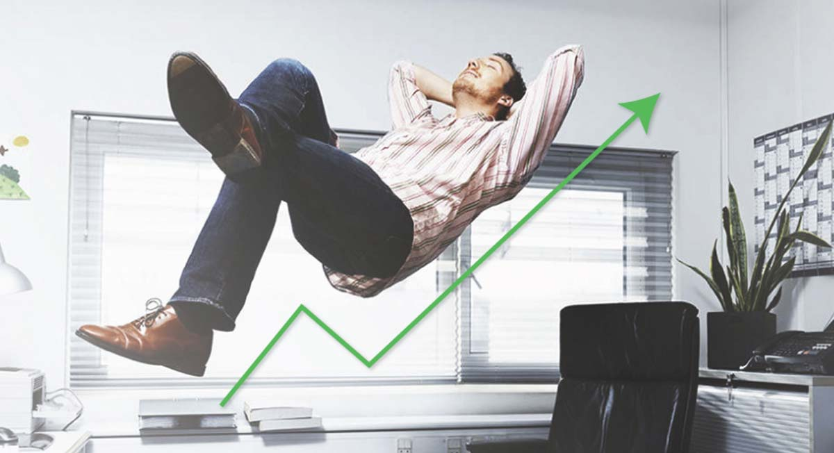 A photo of a relaxed man floating above his desk, over an upward-facing arrow that suggests his business is growing and he is thriving in the gig economy.