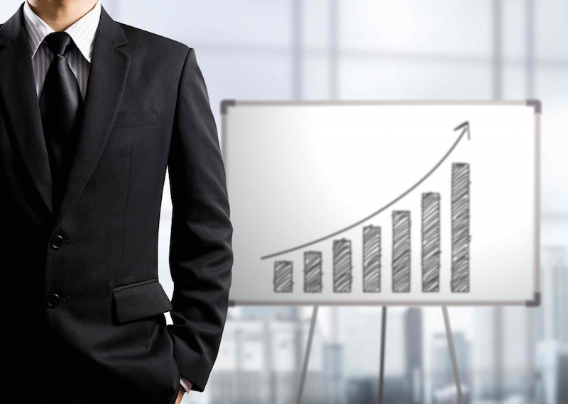 A man is standing in front of a bar graph with an upward-facing​ arrow suggesting business growth and success in scaling his business.