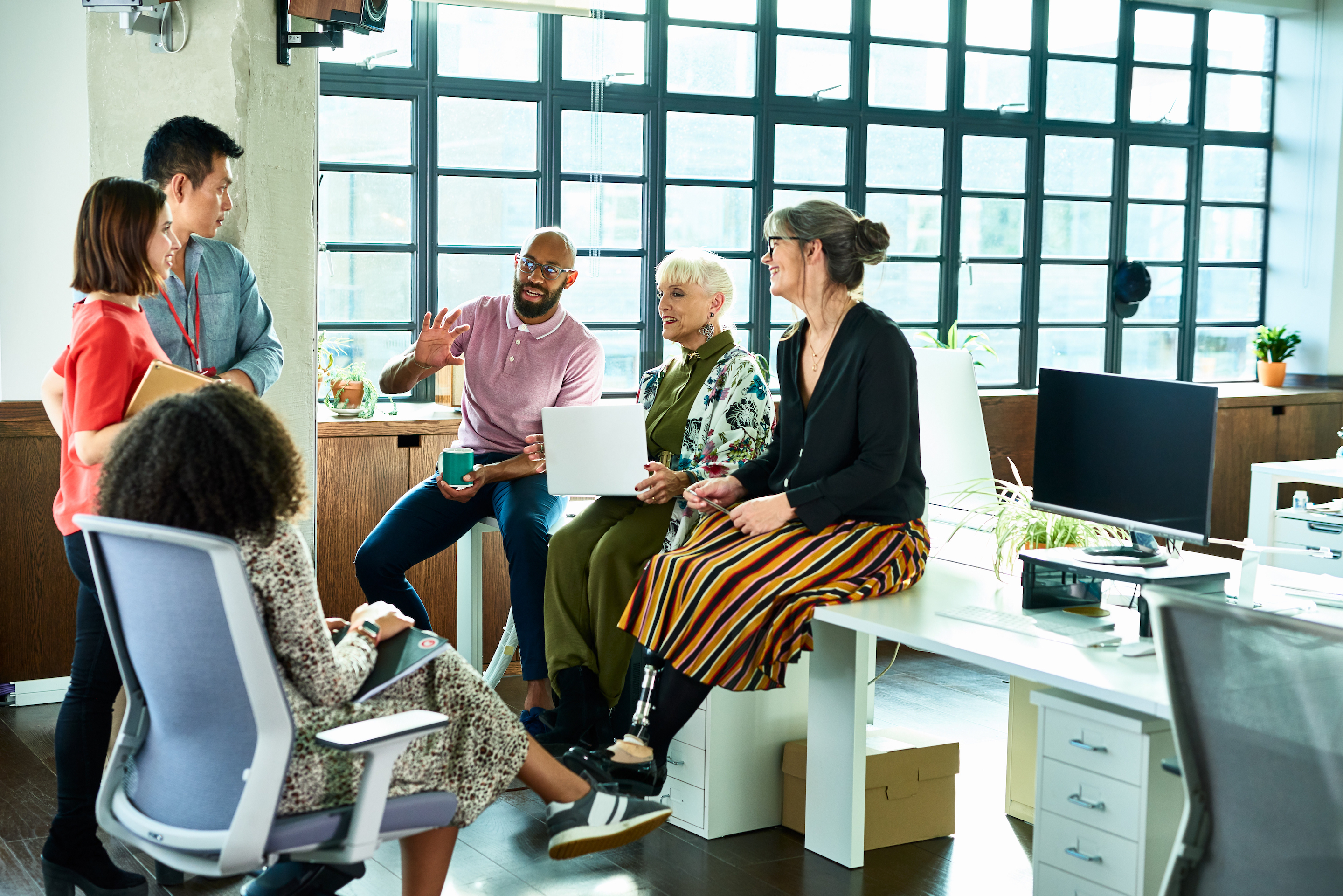A group of freelance talent sits around discussing employment trends and a small business talent strategy. Freelancers are the key to scaling during the 2020 recession.