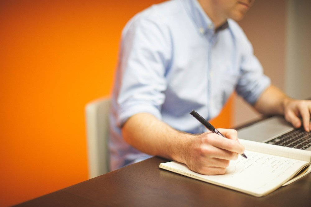 Man writing out his business plan for post-COVID​ and narrowing down the things his business should be doing right now to set himself up for success.
