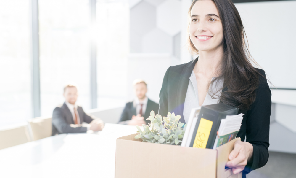 a business professional is walking out with her box of belongings after quitting amid the great resignation