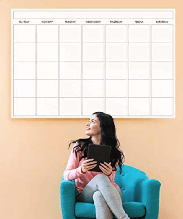 Woman sitting on a cushioned chair holding a tablet in front of a laminated wall calendar